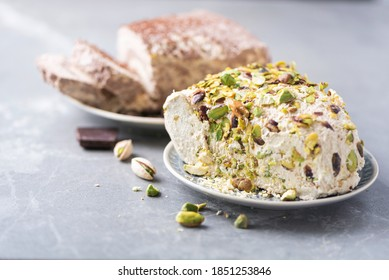 Sesame chocolate halva and halva with pistachios on grey background. Top view. Copy space. Traditional middle eastern sweets. Jewish, turkish, arabic national dessert. Turkish delight.