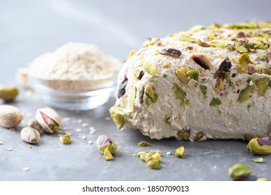 Sesame halva with pistachios on grey background. Top view. Copy space. Traditional middle eastern sweets. Jewish, turkish, arabic national dessert. Turkish delight.