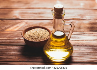 Sesame oil in a glass bottle with a cork and heap sesame seeds in a wooden bowl