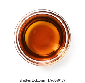 Sesame oil in a glass bowl set against a white background