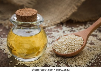 Sesame oil in glass jar and sesame seeds on wooden spoon