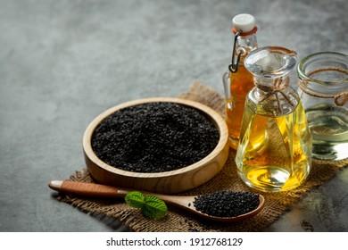 Sesame oil and raw black sesame seeds on dark background