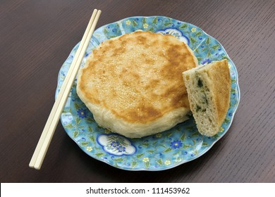 Sesame pancake on a plate with chopsticks on wood surface