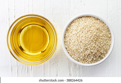 Sesame seed oil and bowl of sesame seeds on white wooden background. Top view