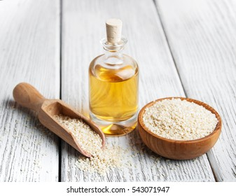 Sesame seeds and bottle with oil on a old wooden table