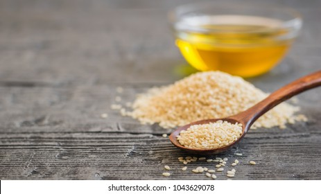 Sesame seeds, oil cup and spoon on dark wooden table.