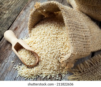 sesame seeds in sack on wooden rustic table