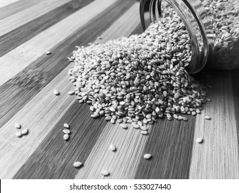 Sesame seeds spilled from the glass jar on a stripped wooden background wallpaper