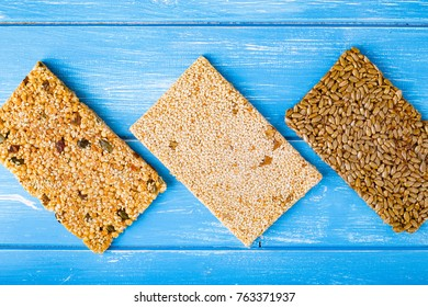 Sesame seeds, sunflower seeds and nuts in caramel glaze on the wooden rustic background.