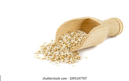 Sesame seeds in a wooden scoop on a white background with copy space for your text