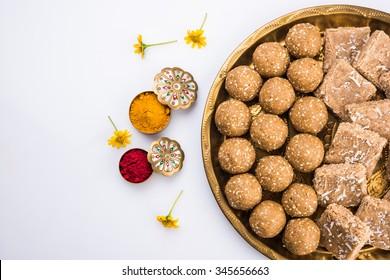 Sesame or Tilgul laddu with haldi kumkum with flowers for Makar Sankranti Festival, selective focus