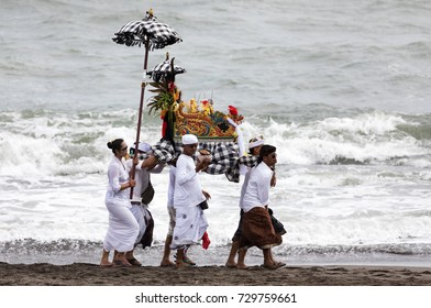 SESEH BEACH, BALI, INDONESIA - MARCH 26 2017 - a group of Hindu worshippers walking on the beach carrying a religious symbol in the lead up to Nyepi Day (Day of Silence)