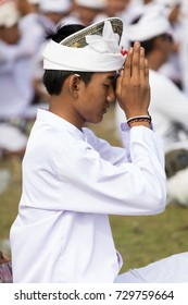 SESEH BEACH, BALI, INDONESIA - MARCH 26 2017 - A Hindu man prays as part of a purification ceremony which forms part of the observance of Nyepi Day (Day of Silence)