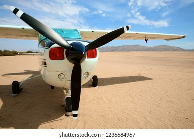 SESFONTAIN, NAMIBIA - DECEMBER 18/2006: Small privcate airplane standing  on the runway in Sesfontein, in the background the Namibian desert against a clear blue sky.