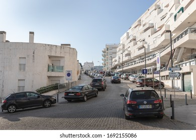 Sesimbra, Portugal - February 20, 2020: View of the city center of Sesimbra by the sea where people are walking on a winter day