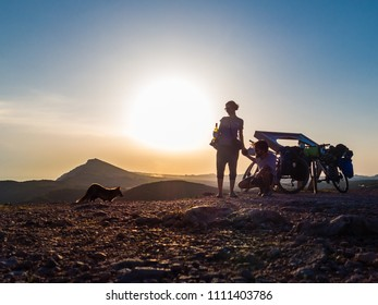 SESIMBRA/PORTUGAL - MARCH 15, 2017: Couple of cyclo tourists encounters a fox, in the Arrabida National Park.