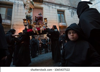 SESSA AURUNCA, ITALY - MARCH 30, 2018 - The Easter parade of black hoods walking through the streets of Sessa Aurunca, carrying the statues of mysteries, the cross, dead Christ and the three Marie