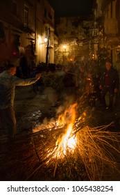 SESSA AURUNCA, ITALY - MARCH 30, 2018 - On Easter Good Friday, at sunset, during the parade of black hoods, men light bonfires on street corners