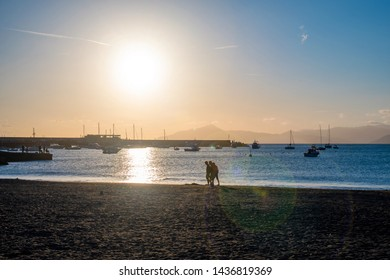 Sestri Levante, Genoa / Italy - April 27 2019: Backlit view of the Bay of Fairy Tales with the silhouettes of three young men walking on the beach, moored boats in the harbor and lens flare at sunset