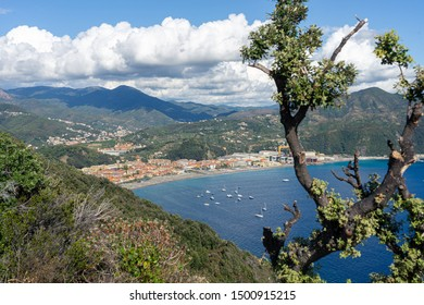 Sestri Levante, Genoa, Italy. View on Riva Trigoso from Punta Manara. Blue sea with tourist boats. In the background Ligurian mountains with white clouds.