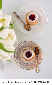 Set for 2 with beautiful white tulips on the foreground. Runeberg's tart or cake is a traditional Finnish dessert and pastry that is served all year round in Porvoo, Finland