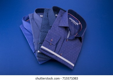 A set of 4 men's shirts in blue tones, folded on a blue background.