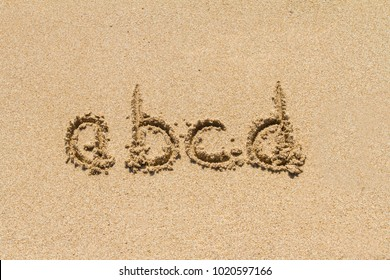 Set of abcd letters of alphabet written on sand with lower case.