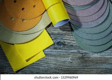 set of abrasive tools sanding discs and sandpaper on vintage wood