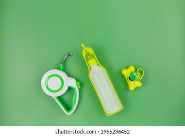 Set of accessories for walking your dog: leash, bottle for water, dog cleaning bags on green background.  				 Pet care and training for pet owners.