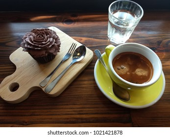 A set of adult waking breakfast consists of yellow cup of doppio or double shot espresso coffee, flower chocolate cupcake on wooden board and glass of drinking water. Placing on natural wooden table.