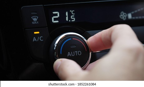 set up air conditioner in the car. Hand turns air conditioner ring. Display indicates temperature inside the car. Cooling air in the car