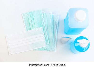 白い背景にアンチウイルスアルコールゲルと保護マスクのセット、医療と医療のコンセプト。