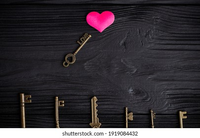 set of antique copper keys. small key with the inscription love, lies on a black wooden background near a pink heart. Heart keys concept, key selection.