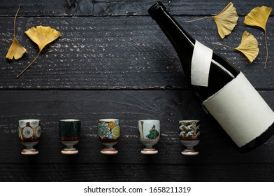 set of antique porcelain shoza style kutani ware sake glasses with dried yellow ginkgo leaves and sake bottle with blank label on dark wooden table and copy space