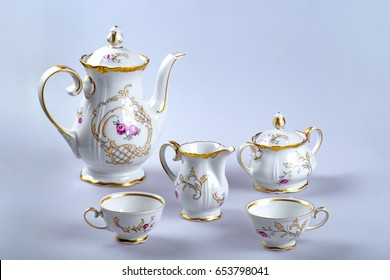 A set of antique tea (coffee) utensils with empty cups on a gray background.