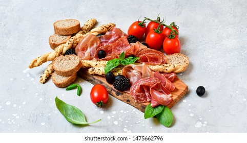 set of appetizers in  italian restaurant prosciutto, salami, bresaola olives tomatoes and grissini bread sticks. Traditional Italian antipasti in Milan, Rome, Florence during aperitif happy hour.