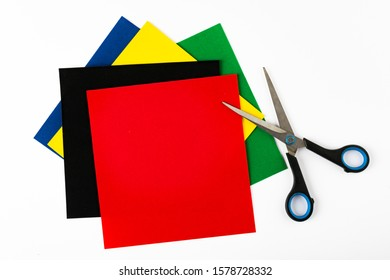 Set for application: paper, scissor. Decoration. Bright red, yellow, green, black and blue sheets of colored velvet paper. White background.  Square, diagonal lines. Top view flat lay with copy space.
