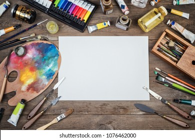 Set of artist accessories collection. Canvas, tube of oil paint, art brushes, palette knife lying on the wood table. Artist workshop background.