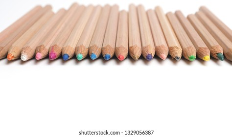 Set of Artist pencils in a row on a white table with space for text, pamoramic image