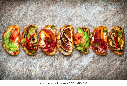 Set of assorted bruschetta  with various toppings for holiday on the stone board. Top view. Party food concept.