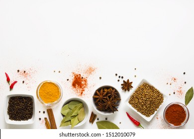 set of assorted colorful spices and herbs in white bowls on a white background, flat lay, top view, with copy space
