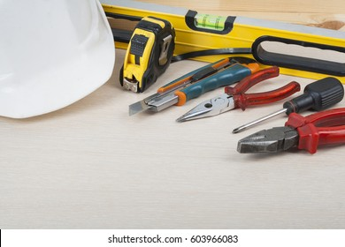 Set of assorted work tools on wood texture background. Copy space for text.