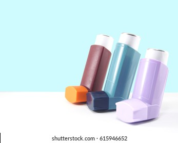 Set of asthma inhalers with blank label on white table. Pharmaceutical product is used to treat lung inflammation and prevent asthma attack for asthma/COPD patients. Health and medical concept.