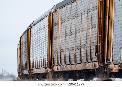 A set of autoracks (railway cars carrying automobiles) rounds a bend on a winter's day.