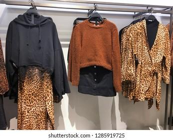 Set of autumn coats , Leopard pattern  clothes shirts, jacket ,sundress hanging on rack shopping.