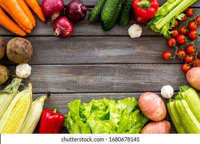 Set of autumn vegetables - potato, cucumber, carrot, greenery - on dark wooden background top-down copy space frame