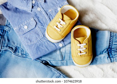 Set of baby boy clothes in color blue that includes denim pants, striped polo, and shoes