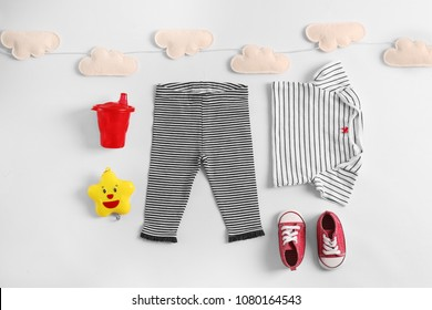 Set of baby clothes and accessories on light background, flat lay