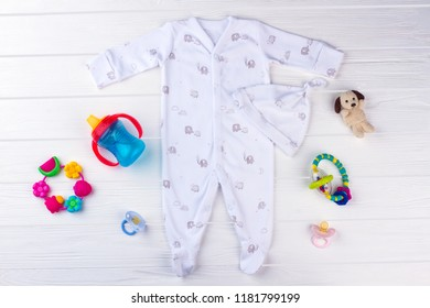Set of baby clothes and necessities. White baby pajama with knot hat printed with elephants, plush dog, rattles, bottle and pacifiers.