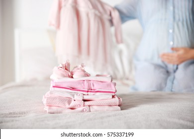 Set of baby clothes on bed and pregnant woman on background